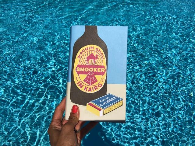 Annette König hält das Buch von Waguih Ghali: «Snooker in Kairo» vor blaues Wasser