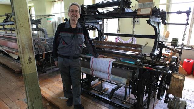 Hans Hiestand steht vor einer Webmaschine, an der ein weisses Küchentuch mit roten Streifen gewebt wird.