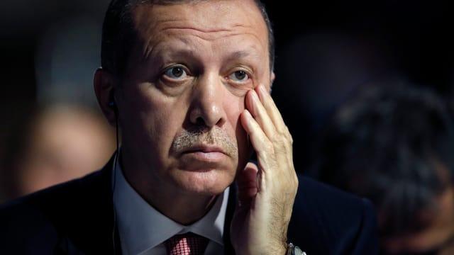 Nahaufnahme von Erdogans Gesicht, die linke Hand reibt sich an der Backe unter dem Auge.
