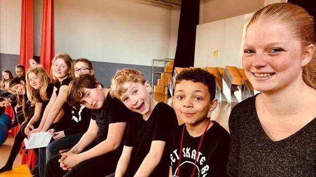 Kinder und Jugendliche sitzen in einer Reihe