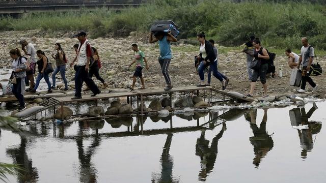 Eine Gruppe Flüchtlinge überquert mitsamt Koffern und Taschen via Holzsteg einen Fluss.