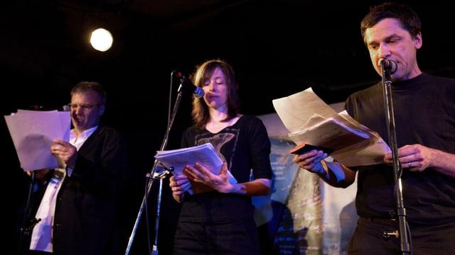 Drei Autoren stehen auf der Bühne und lesen.