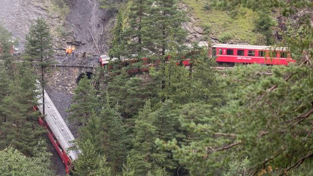 Im Vordergrund stehen Bäume und verdecken teilweise die Sicht auf 2 rote RhB-Wagen. Diese sind entgleist, aber stehen noch auf dem Trasse. Links im Bild ist der Erdrutsch über die Bahngleise und den heruntergestürtzten Bahnwagen zu sehen.