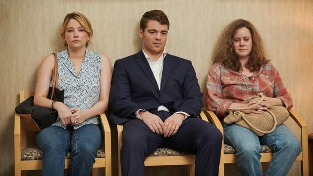 Eine junge Frau, ein junger Mann und eine ältere Frau sitzen nebeneinander auf Stühlen.