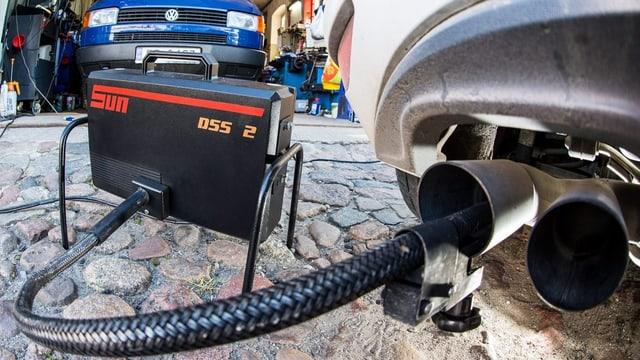 Abgastest: Ein in einem Auspuff befestigter Schlauch führt in einen Apparat, der wie ein Koffe aussieht. Im Hintergrund ein blauer VW.