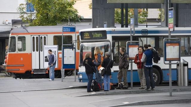 Menschen warten an einem Bahnhof.