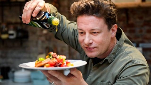 Oliver träufelt Olivenöl über einen angerichteten Teller mit Essen.