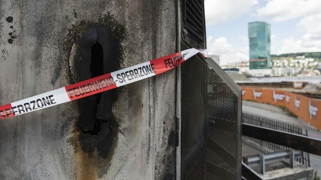 Ein nach einem Brandanschlag beschädigter Gebäudeteil mit Absperrband.
