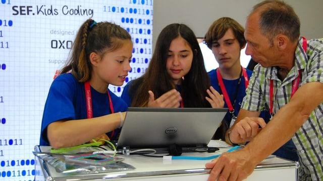 Ein Lehrer und die Schüler mit Laptop.
