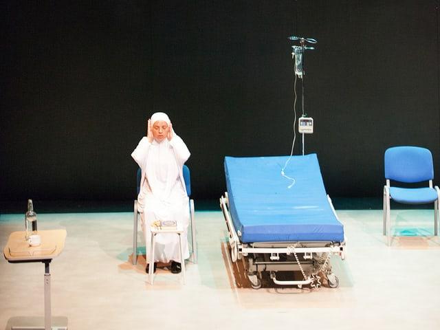 Theaterszene: Eine Frau in weiss sitzt klagend neben einem blau bezogenen Bett.
