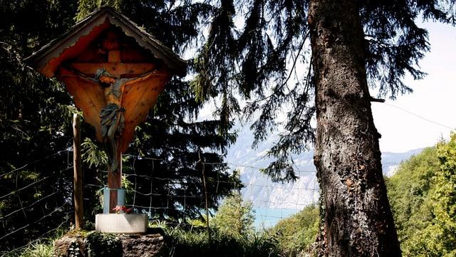 Ein hölzernes Wegkreuz mit Jesus zwischen Bäumen zwischen Sisikon nach Riemenstalden im Kanton Uri.