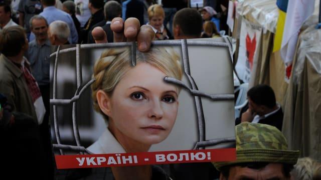 Demonstranten halten ein Bild der inhaftierten Timoschenko in die Kamera des Fotografen.