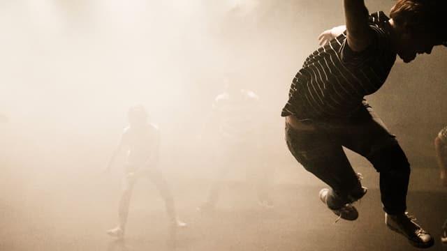 eine junge Frau auf einer Theaterbühne, in Nebel getaucht