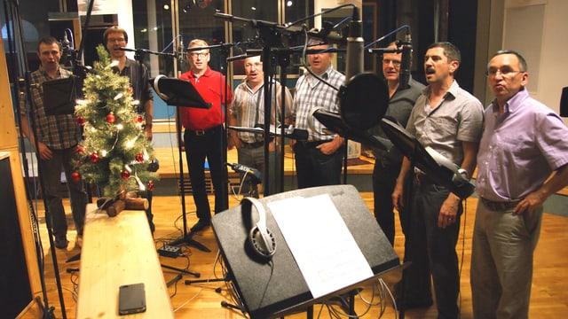 Acht Sänger im Studio vor Mikrofonen.
