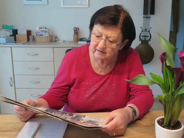 Eine Frau sitzt an einem Tisch und liest Zeitung