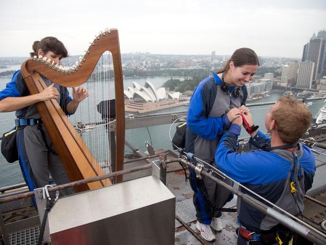 Harfenspielerin und ein Paar, alle angegurtet auf der Harbour Brigde.