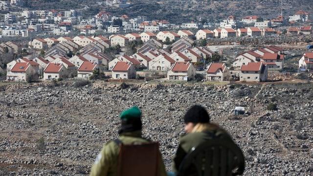 Zwei Soldaten von hinten stehen leicht erhöht und schauen auf die Siedlung mit Dutzenden gleichen Häusern.