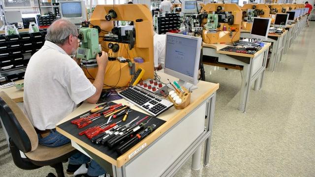 Mitarbeiter der Leica Geosystems kontrolliert ein Gerät für Bauvermessungen.