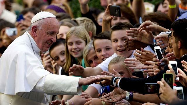Papst Franziskus in weissem Gewand vor vielen Jugendlichen, die Smartphones in den Händen halten.