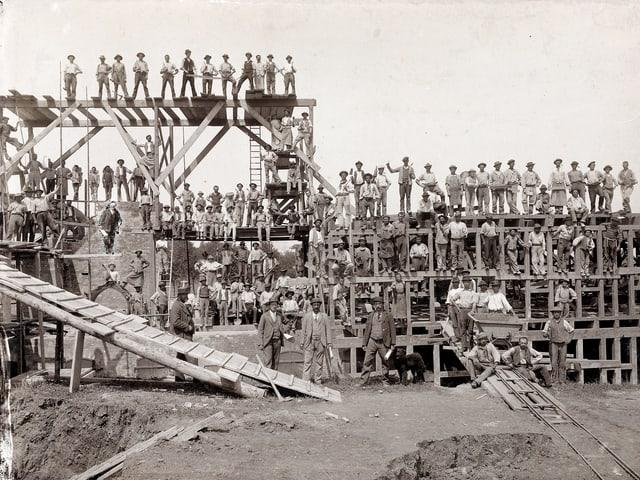 Gerüste und Rampen aus Holz. Darauf viele Arbeiter, die meisten mit Hüten.