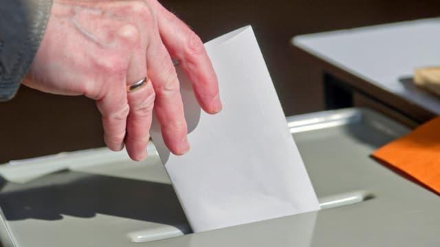 Eine Wähler legt einen Wahlzettel in die Urne.