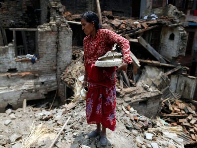 Eine Frau mitten in Ruinen.