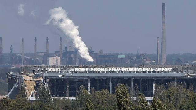 Halb zerstörtes Gebäude des Donezker Airports mit beschädigtem Schriftzug. Rauch steigt auf.