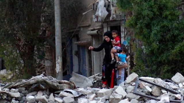 Eine junge Frau klettert mit zwei Kindern über Feld mit Schutt.