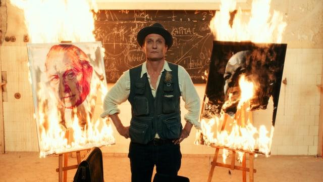 Mann vor brennenden Plakaten.