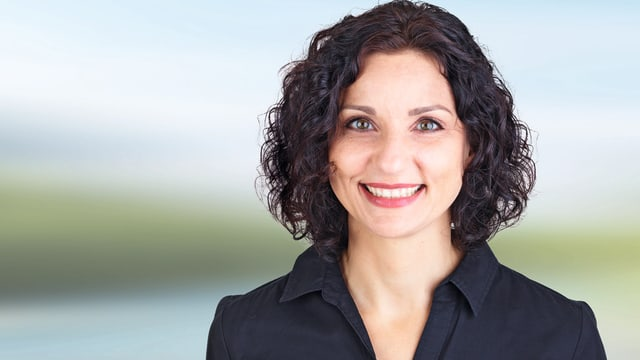 Wahlbild Politikerin Gabriela Suter. Breites Lachen. Schwarze, lockige Haare.