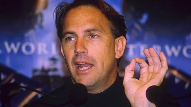 Portrait eines Mannes vor dem Mikrofon.