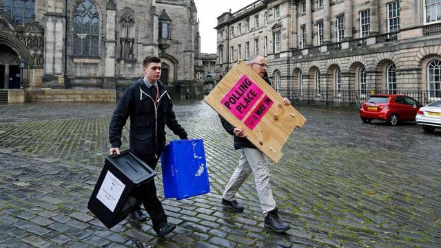 Wahlhelfer tragen Urne