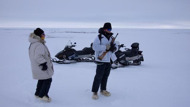Zwei Menschen stehen im Schnee, der eine hält ein Gewehr im Arm, im Hintergrund zwei Schneemobile.