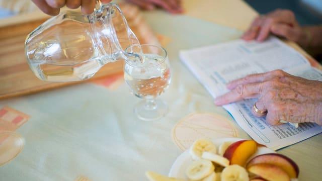 Eine Dame schenkt einer Seniorin Wasser ins Glas
