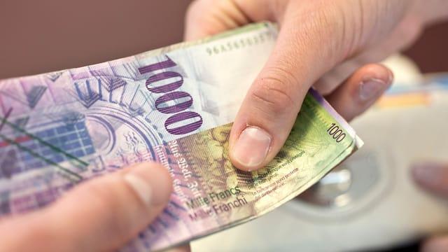 Eine Tausendernote wird von einer Hand in die andere gegeben.