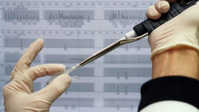 Laborant mit Handschuhen arbeitet mit Pipette