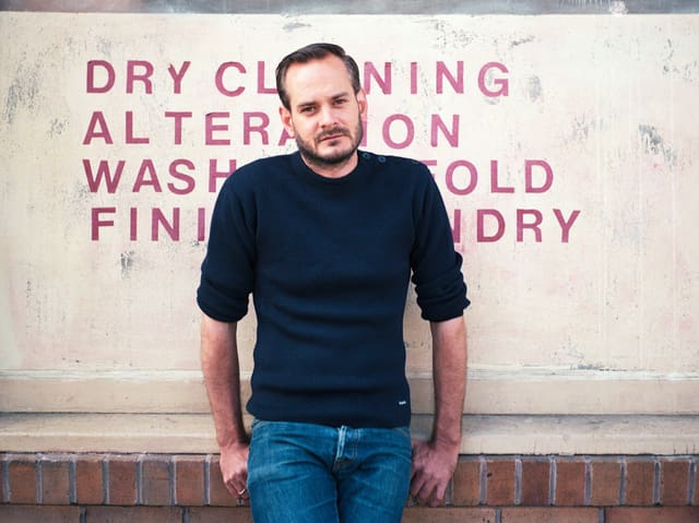 Ein Mann in dunkelblauem Pullover steht vor einer Wand.