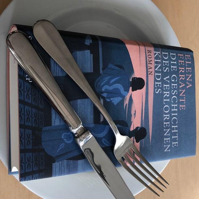 Das Buch «Die Geschichte des verlorenen Kindes» von Elena Ferrante liegt auf einem weissen Teller. Messer und Gabel nebeneinander darüber.