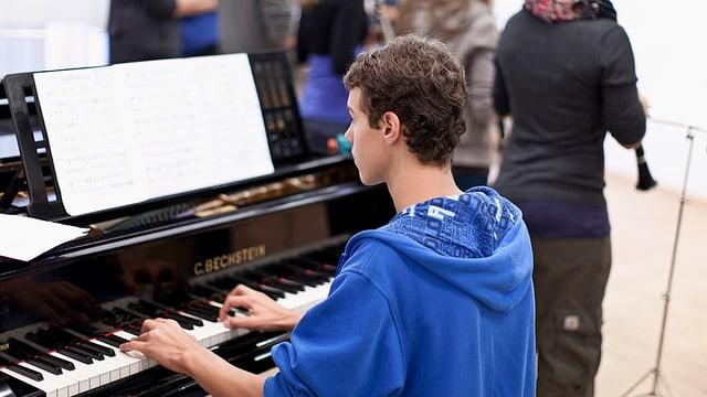Junger Mann spielt ein Musikstück am Klavier.