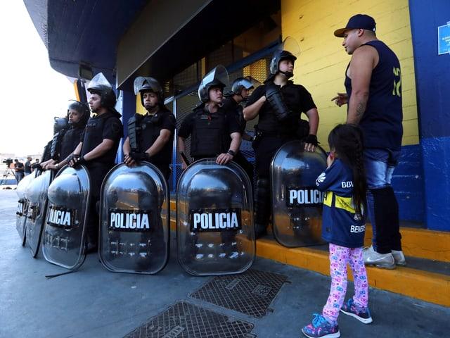 Polizeikräfte stehen mit Schutzschildern auf der Strasse.