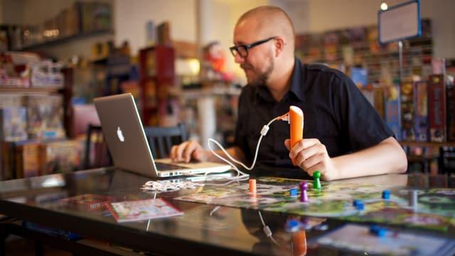 Spieleautor Ulrich Blum testet ein Spiel für die stiftförmige Tiptoi-Konsole vor seinem Notebook.