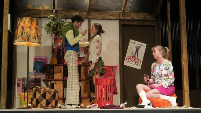 Szene in einem Landtheater: Ein Paar diskutiert stehend auf der Bühne, daneben sitzt eine junge Frau auf einem Hocker.