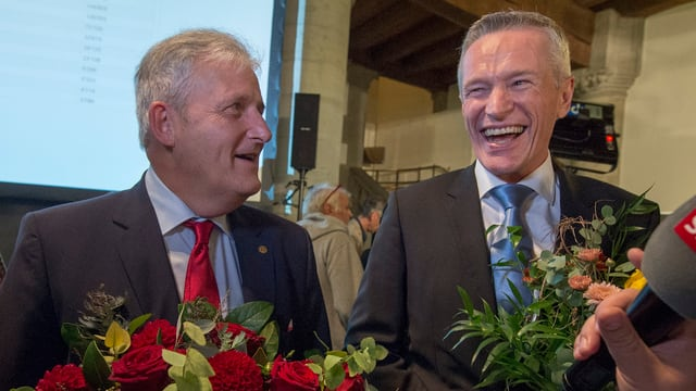 Die Ständeräte Luginbühl und Stöckli mit Blumensträussen in den Händen.