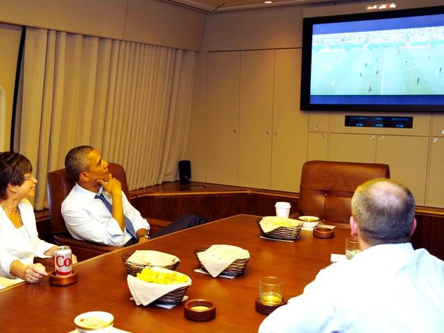 Barack Obama schaut mit zwei Personen in der «Air Force One» ein Fussballspiel im Fernsehen.