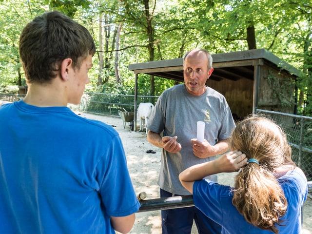 Zooangestellter und zwei Kinder, der Mann weist die Kinder an, was zu tun ist.