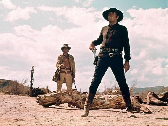 Filmszene: Ein Mann in Schwarzer Kleidung mit Cowboy-Hut greift nach seinem Revolver. Hinter ihm steht ein anderer Mann, der seine Pistole auf ihn richtet.