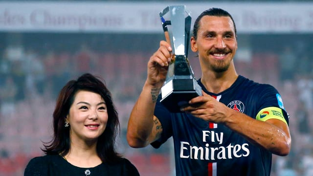 Zlatan Ibrahimovic präsentiert in Peking die französische Supercup-Trophäe.