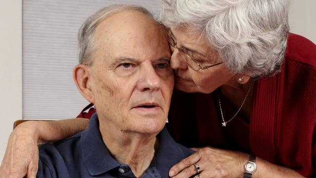 Ältere Frau hält ihre Wange an die Schläfen eines älteren Mannes.
