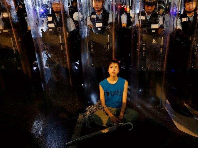 Frau demonstriert sitzend vor Polizisten