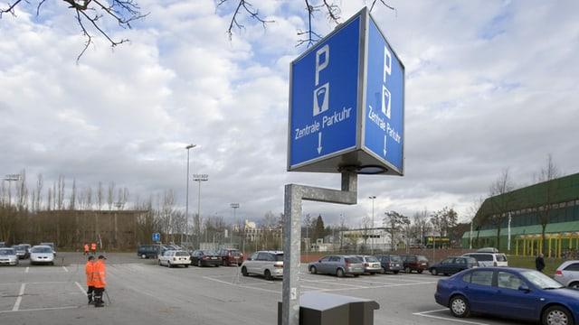 """Parkuhr mit Schild """"Zentrale Parkuhr"""" bei grossem Parkplatz"""